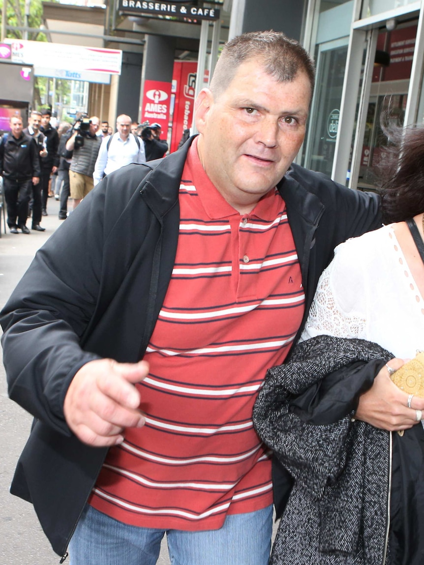 Michael Rogers, wearing a black jacket over a red polo shirt with white stripes, walks down a CBD street.