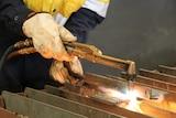 A boiler maker using a welder.