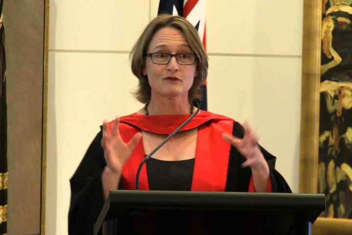 一名穿着教授袍的白人女性在讲台上发表演讲