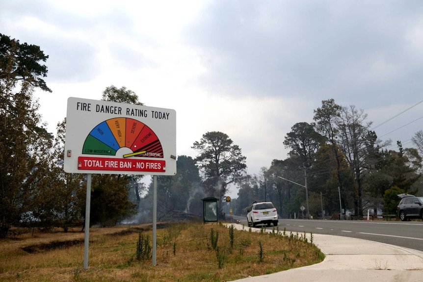 A fire danger rating sign by the roadside is pointed to 'catastrophic' as smoking embers can be seen behind.