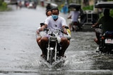 Residents on a motorcycle negotiate a flooded road due to Typhoon Molave in Vietnam.
