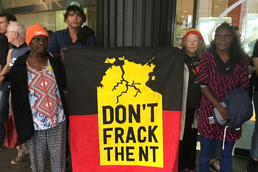 """The traditional owners hold a sign saying """"Don't frack the NT""""."""