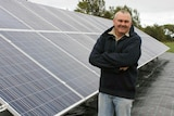 Rodney Locke stands next to a long row of solar panels.