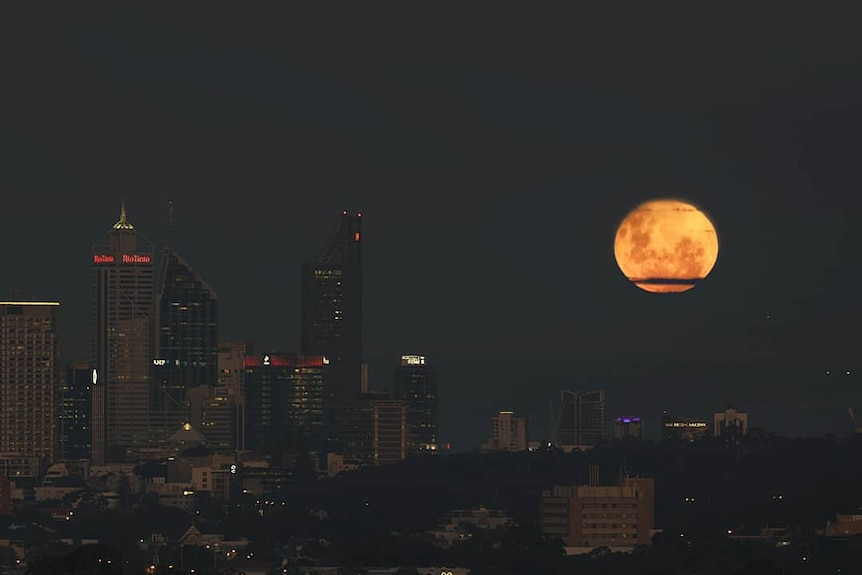 A full moon above a city at night.