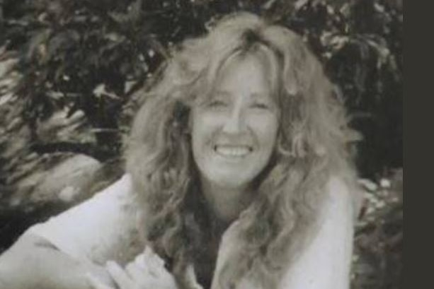 A woman with long hair smiles at the camera