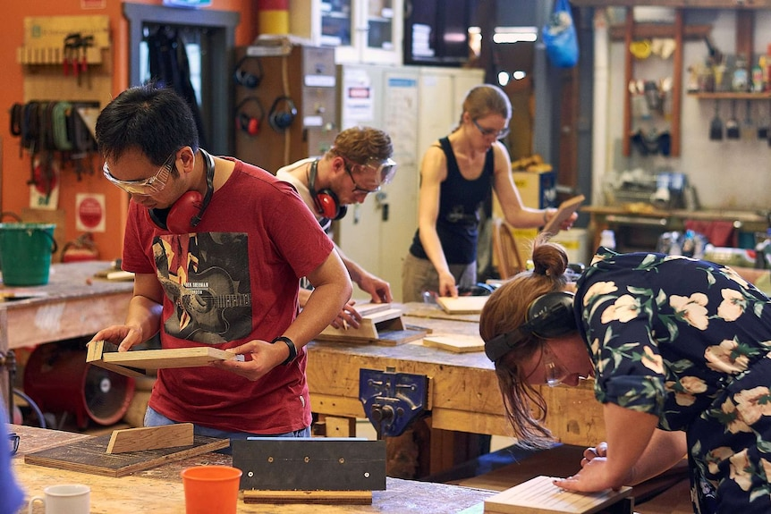 A group of people stand in a workshop wearing personal protective equipment working on wood products.