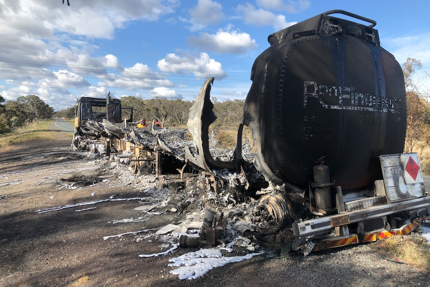 A petrol tanker is seen burnt out on the highway