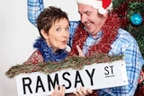 A man and a woman wrapped in Christmas decorations holding a street sign that says Ramsay St.