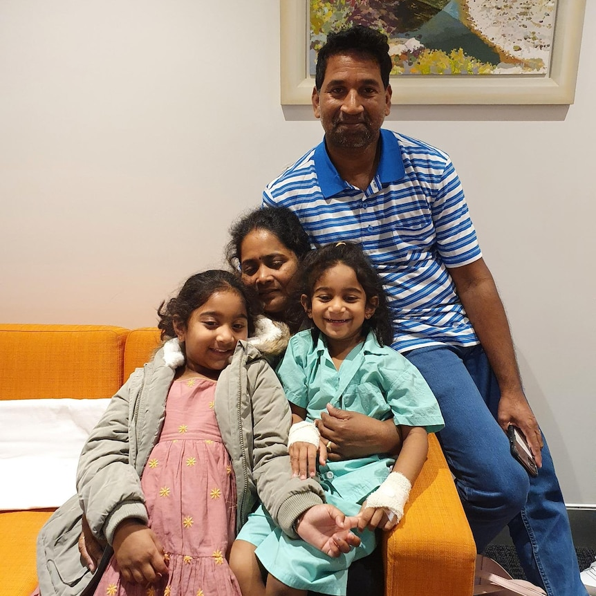 A close-up photo of the Murugappan family with a painting in the background.