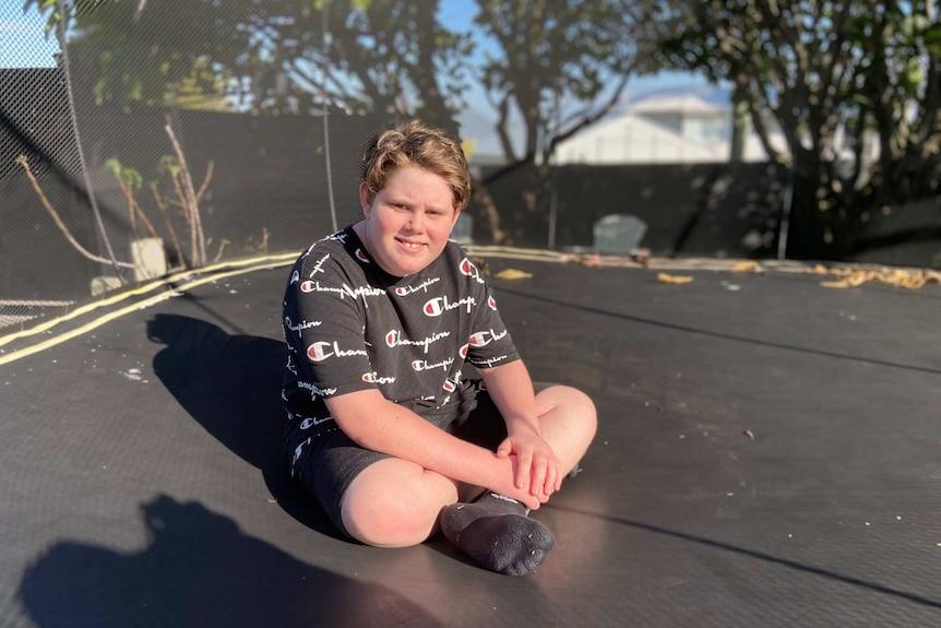 Remi Seminara sits on a trampoline.