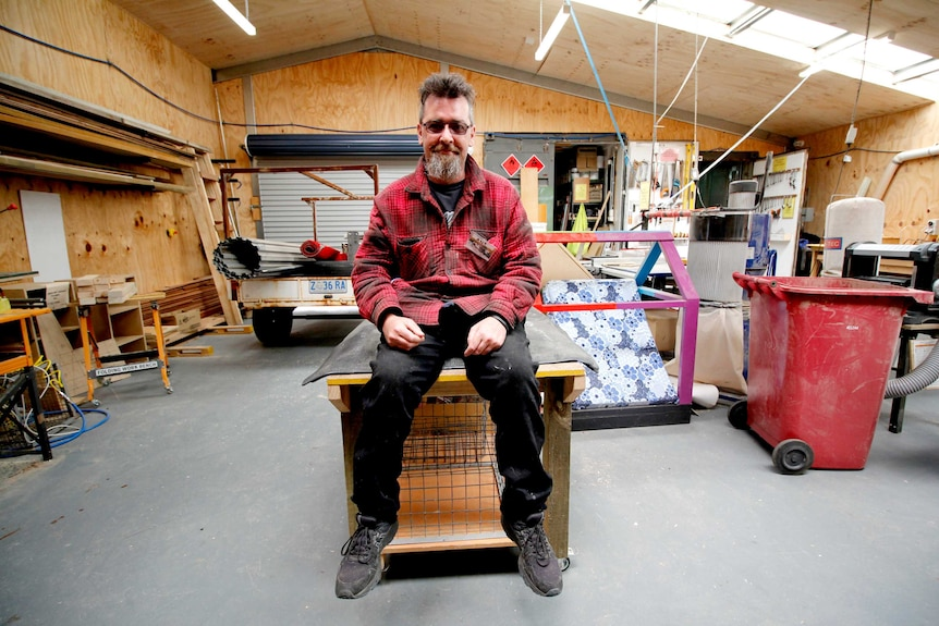A man sits on a workbench in a men's shed surrounded by equipment
