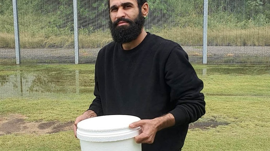 Amin Afravi collects rainwater in a bucket at the Brisbane's Immigration Transit Accommodation.