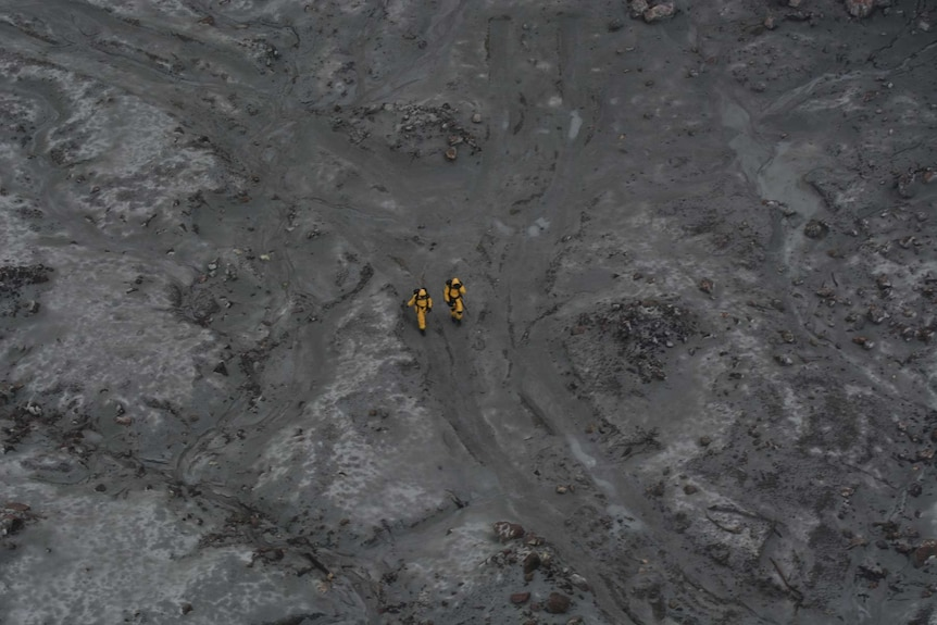 An aerial image of two people in yellow suits walking on a barren landscape