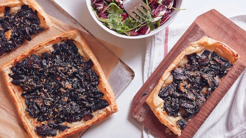 One and half mushroom tarts sitting on a baking tray, a greens and radicchio salad, and half tart on a chopping board, for lunch
