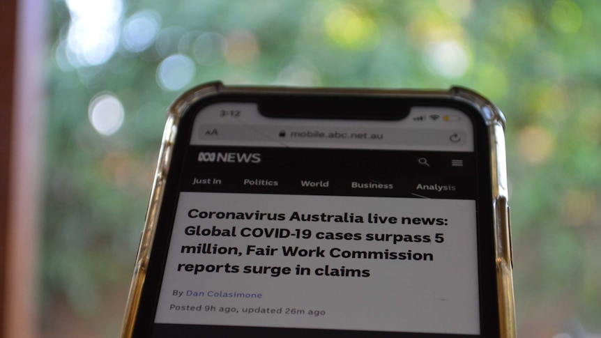 Close up of phone with Coronavirus Australia live news blog on screen.