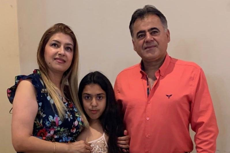 Arsalan Sadeghi Iveli stands next to his wife and daughter.