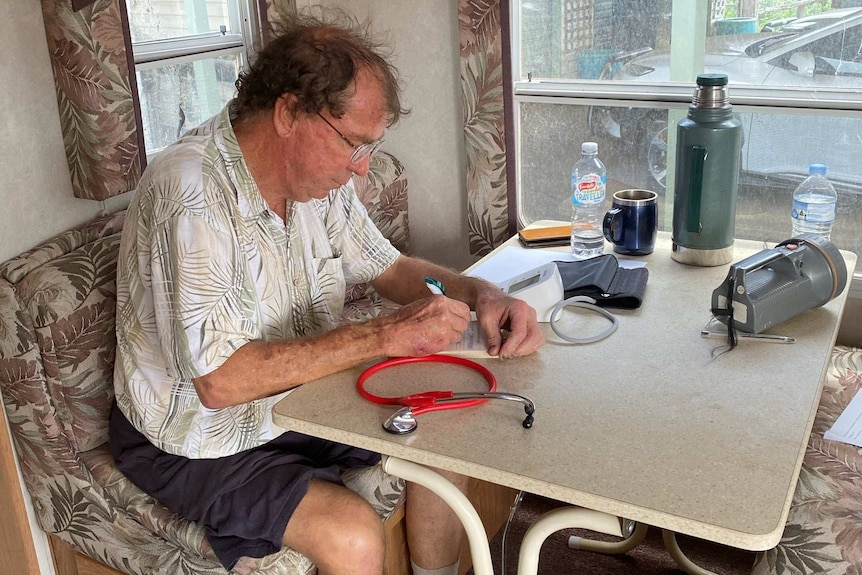 Dr Lee takes notes in caravan for his patients