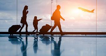 A family of three walk through an airport as a plane takes off.