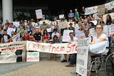Protestors hold signs in protest at Lady Cilento Children's Hospital