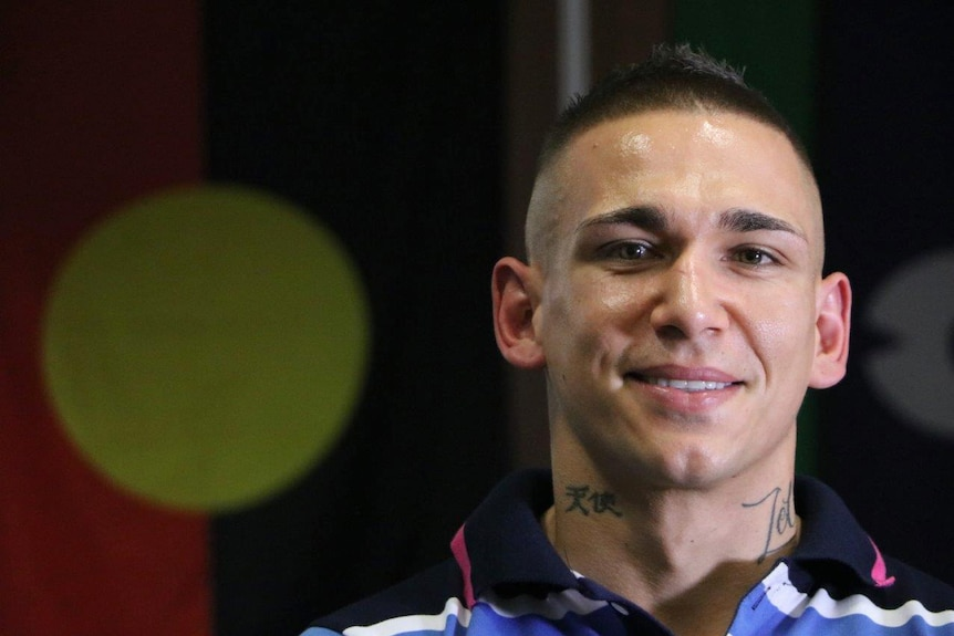 Marlon Johns standing in front of an Aboriginal flag at St Catherine's.