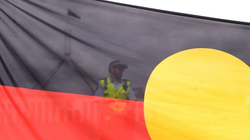 A semi-transparent indigenous flag in front of a police officer, with Parliament House in the background.
