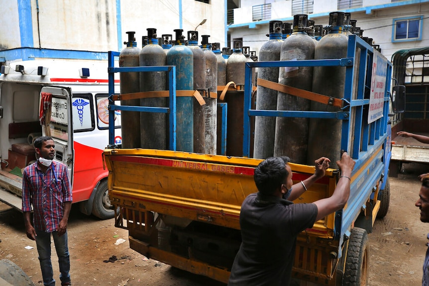 A man closes a trailer of a small truck, which carrries rows of empty oxygen canisters.