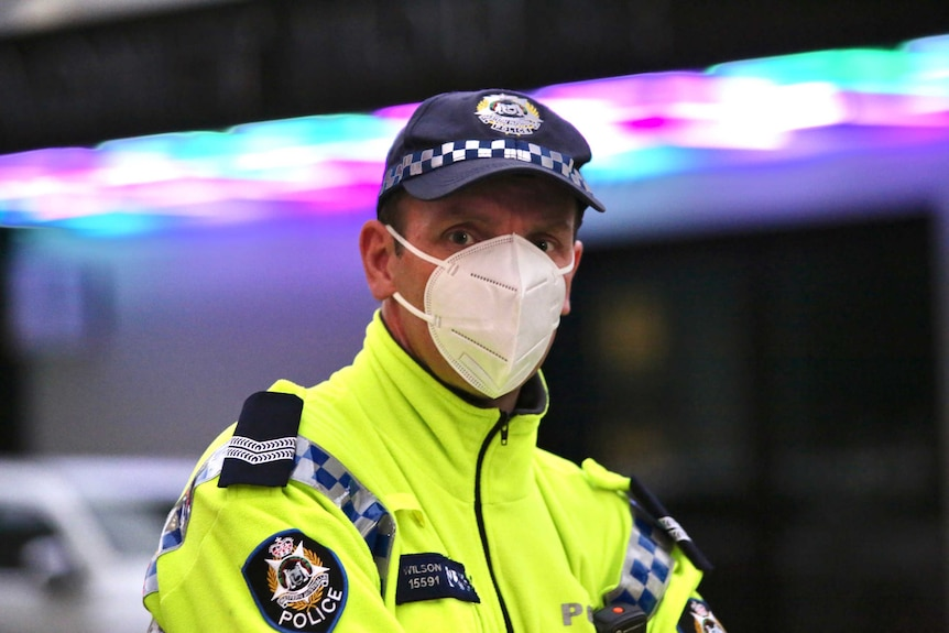 A police officer wearing a fluoro yellow jacket and white face mask stares into the camera intently.
