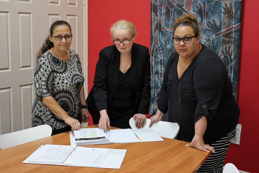 Three professional women stand around a table looking at documents