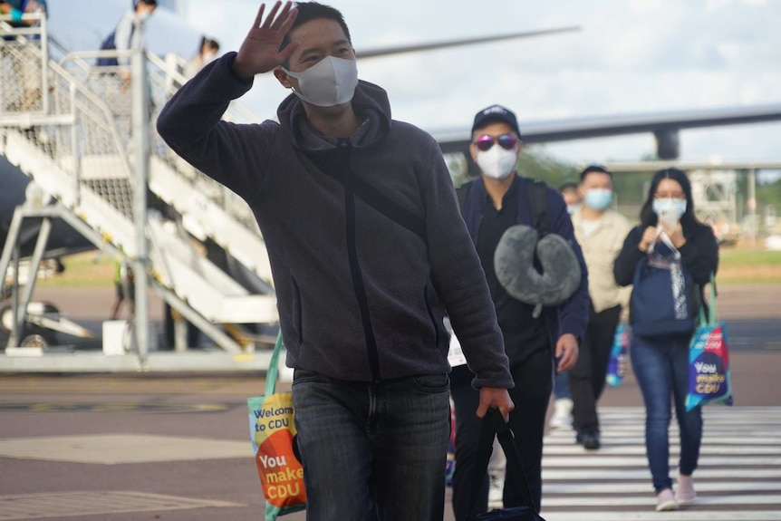 A student wearing a face mask waves on the Darwin Airport tarmac with other students walking behind him.