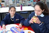 Sara Manjeh sniffs a jar of Vegemite during her school's integration class.