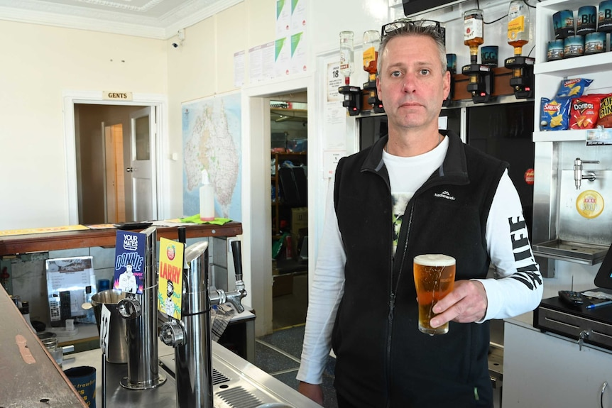 A man with greying hair stands behind the bar at a pub wearing a vest and holding beer.