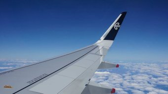 A jet's wing above clouds, seen through a plane window.