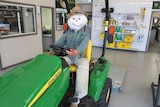 smiling scarecrow driving tractor