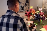 The back of a man making origami flowers.