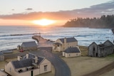 The sun sets over the water off Norfolk Island. On the land in the foreground, historic buildings face the ocean.