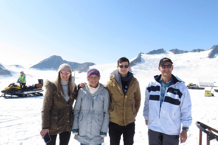Four people stand in a line on a glacier.
