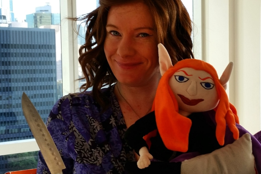 Woman holds a knife and a stuffed toy pixie.