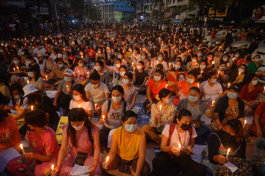A huge group of sitting protesters, many wearing face masks, raise candles in their hands.
