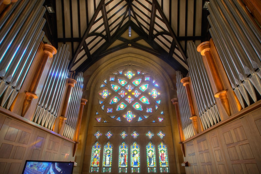 The inside of a church, including stained glass windows and the pipes of an organ.