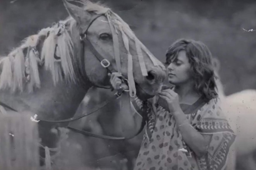 A young girl pats her horse.
