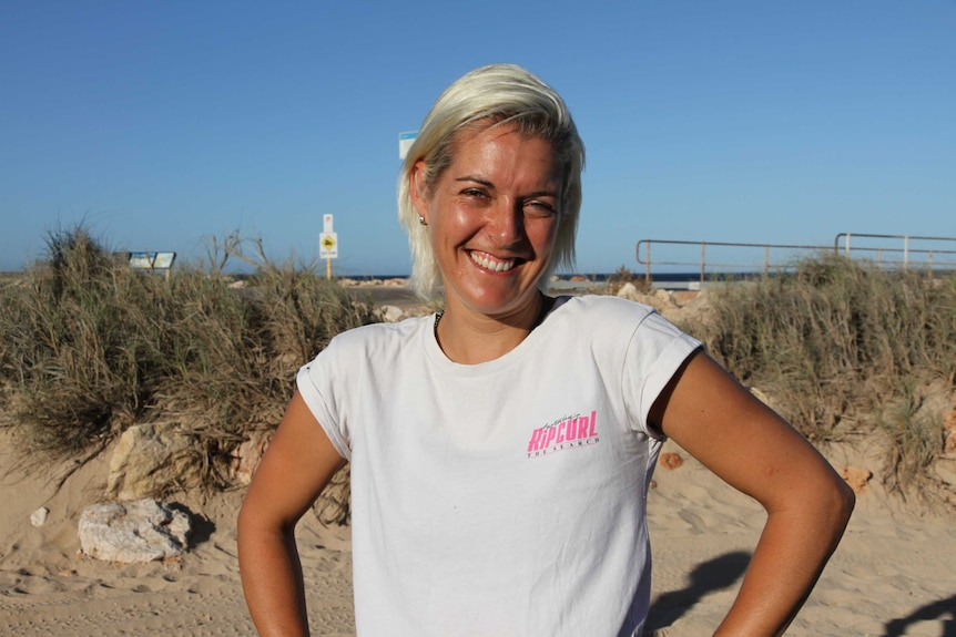 A blonde woman in a white t-shirt grins with her hands on her hips at a beach.