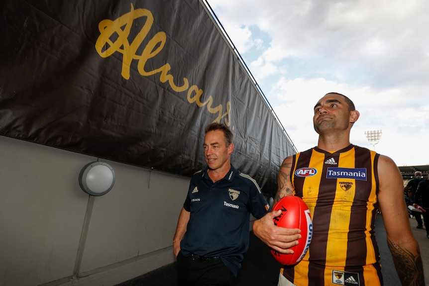 A coach and a veteran player walk down the player's race at the MCG after their final AFL games for Hawthorn.