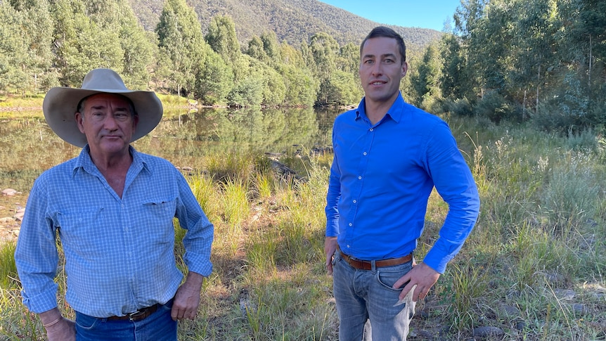 Two men in blue shirts stand with their hands on their hips along a stretch of river.