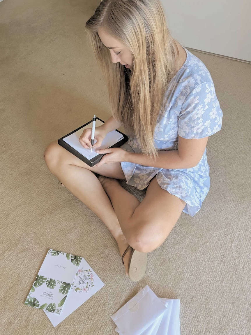 A woman sitting on the flood writing a letter
