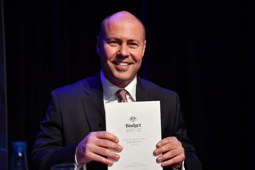 A very smiley Josh Frydenberg holds the budget in front of him.