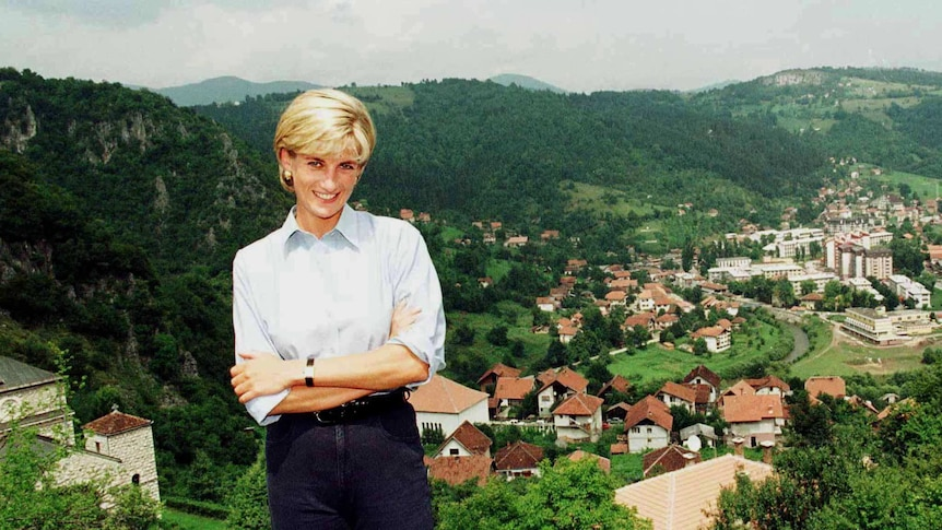 Princess Diana smiles while standing on top of a plateau with a Bosnian village nestled between green hills in a valley below.