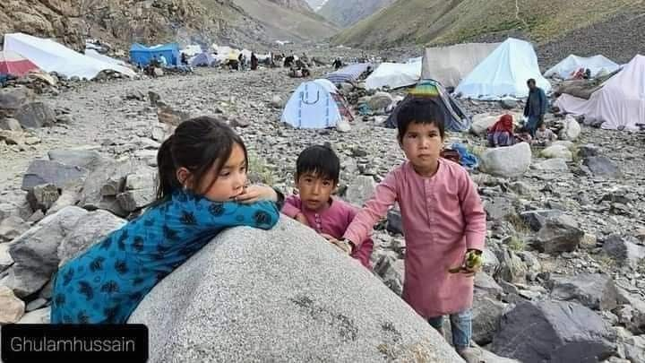 Children play around rocks as tents stand in the distance.