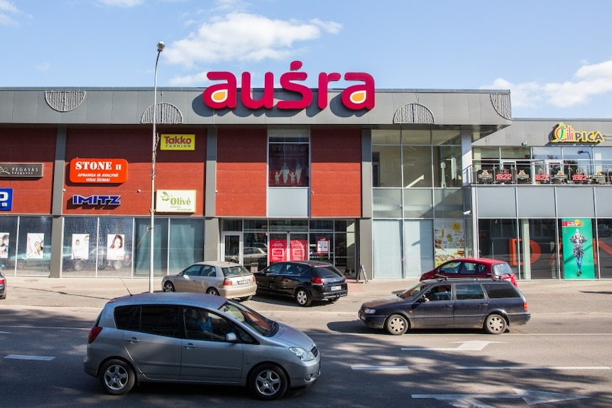 The facade of a shopping centre in Lithuania, with cars parked in the foreground.
