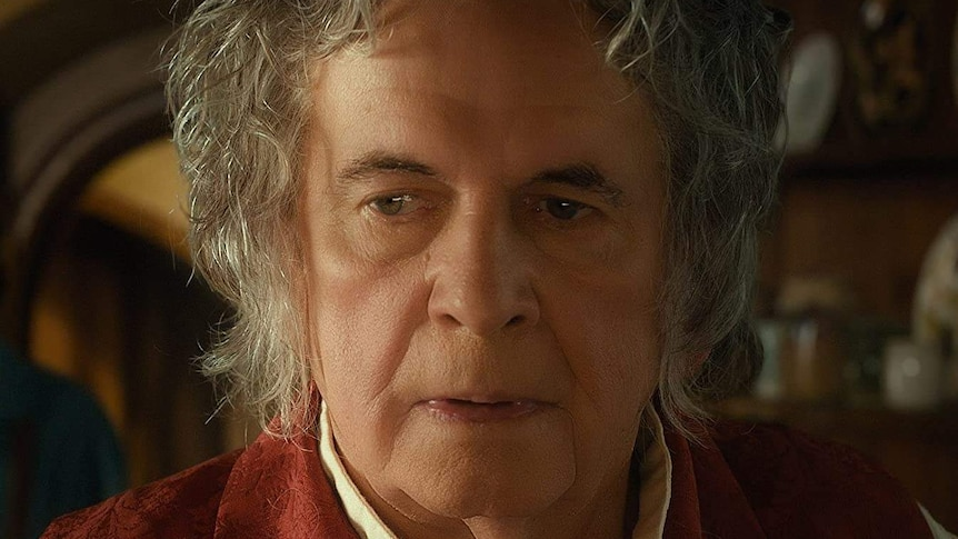 Ian Holm with long white hair looking offscreen