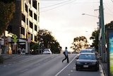 Woman wearing a mask crosses a street at Brisbane's West End at sunset.
